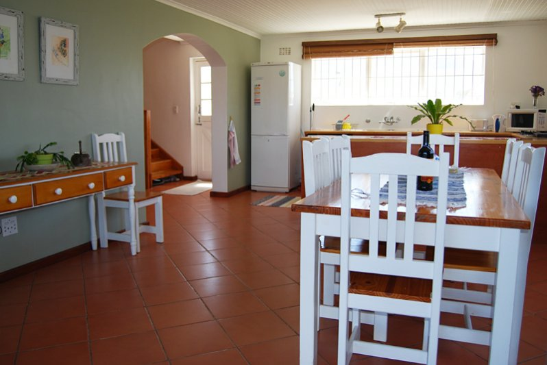 Open plan dining room between fully equipped kitchen and outdoor braai under roof.