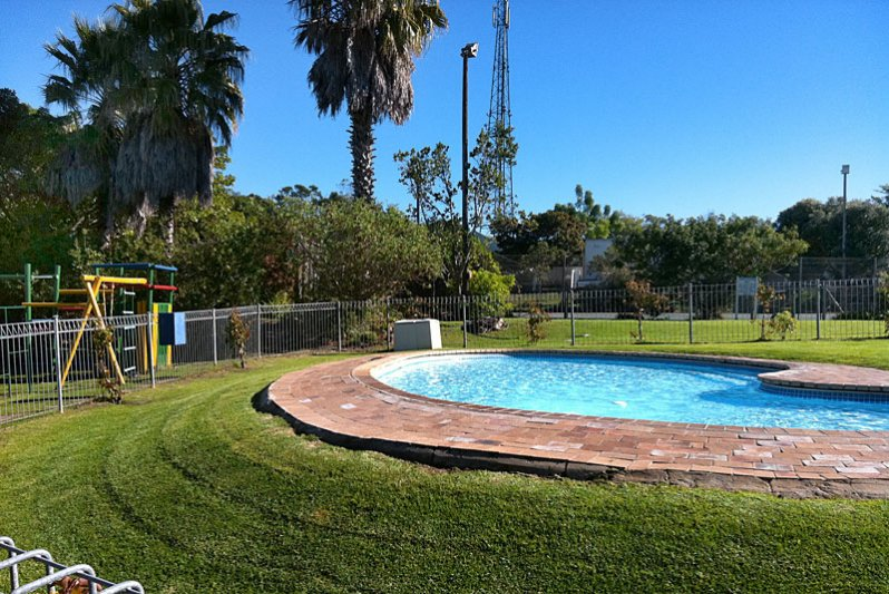 Kids pool with jungle gym and tennis court in background