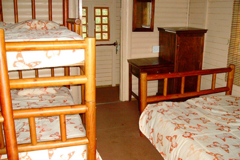 Two log cabins with a double bed and a bunker bed.